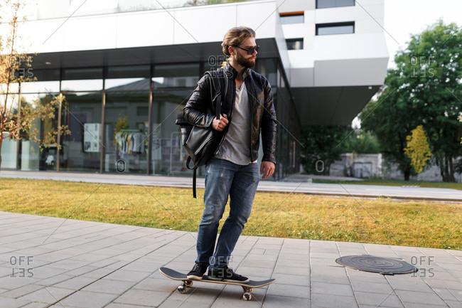 The stylish handsome boy skating at a university