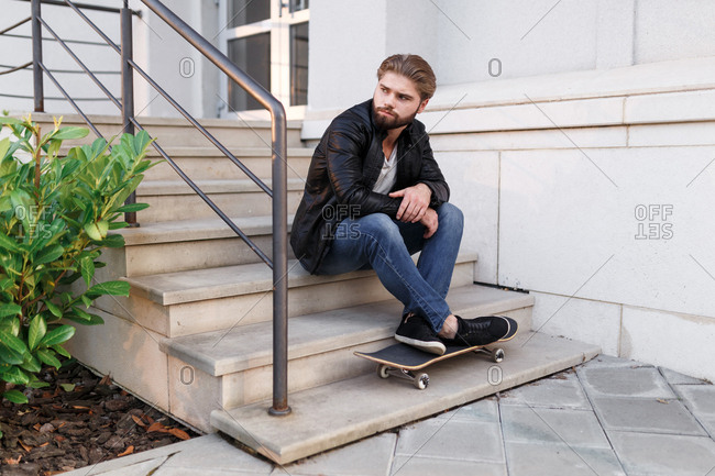 The stylish handsome boy with skateboard is chilling near the university