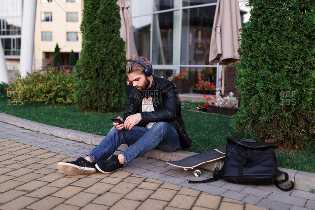 The stylish handsome boy with skateboard is chilling near the university and listening to music