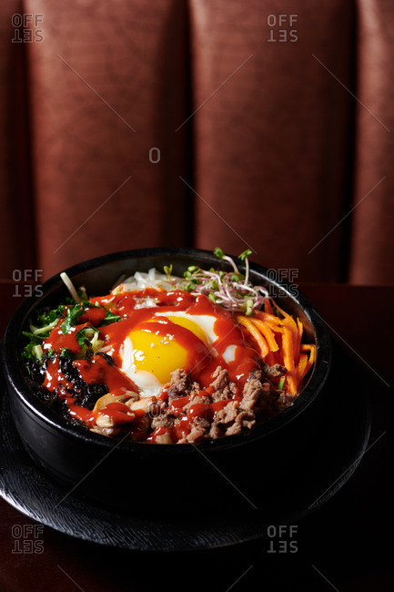 Classic Korean dish of bibimbap served in a black bowl with a sunny side up egg, beef, and stir fried vegetables