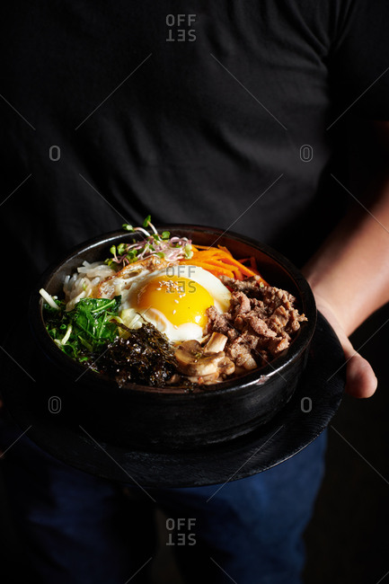 Hands of server holding a bibimbap dish with a sunny side up egg, beef, and veggies in a dark bowl