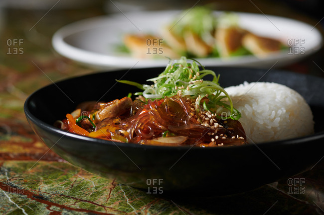 Japchae Bap Korean dish in a restaurant with glass noodles stir fried with vegetables on a stone jade green surface