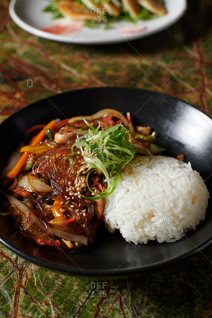 Japchae Bap Korean dish with glass noodles stir fried with vegetables on a stone jade green surface