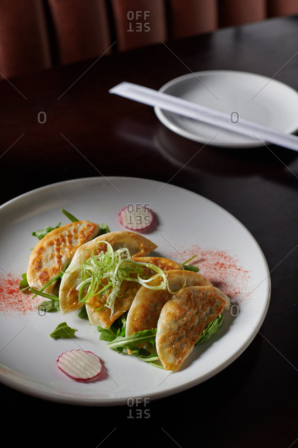 Pan seared pot stickers served at a Korean Restaurant garnished with arugula, radish and green onions