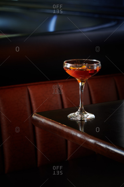 Old Fashioned cocktail of whiskey with a orange twist served in a stemmed glass in a bar