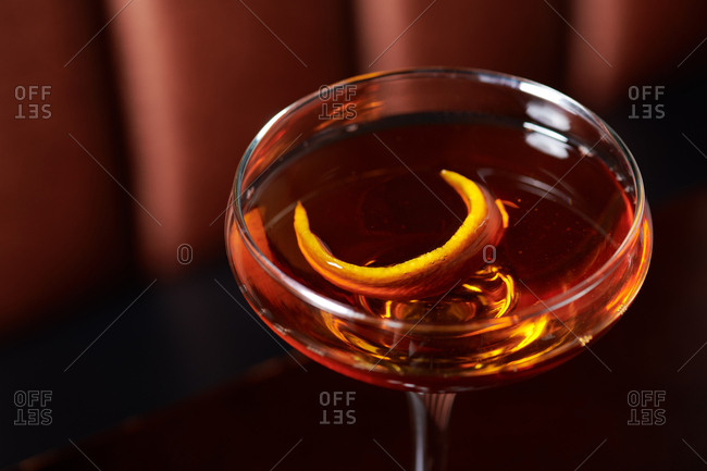 Old Fashioned cocktail of whiskey with a orange twist served in a stemmed glass