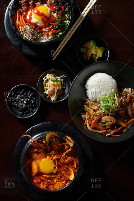 Various Korean dishes including japchae bap, bibimbap and sundubu-jjigae, in a Korean restaurant from above