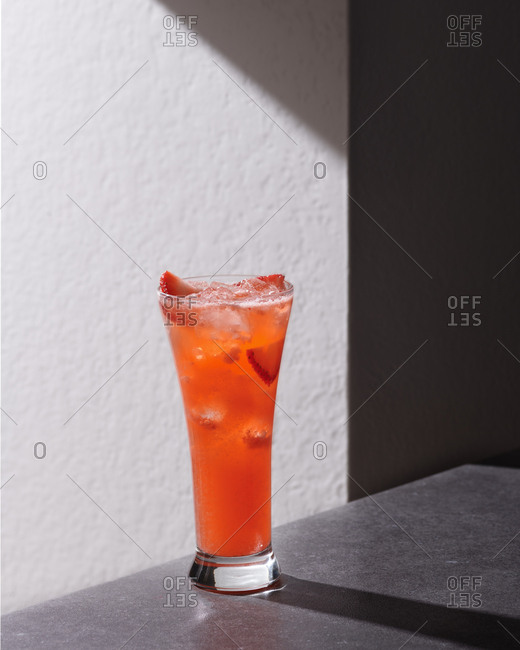 Strawberry cocktail with ice on a stark monochrome background