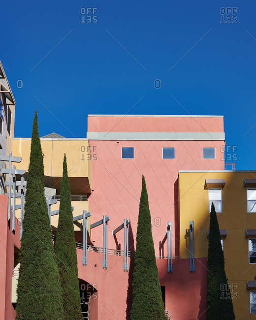 Pastel exterior of pinks and yellows with cone shaped conifer trees in front in San Diego California