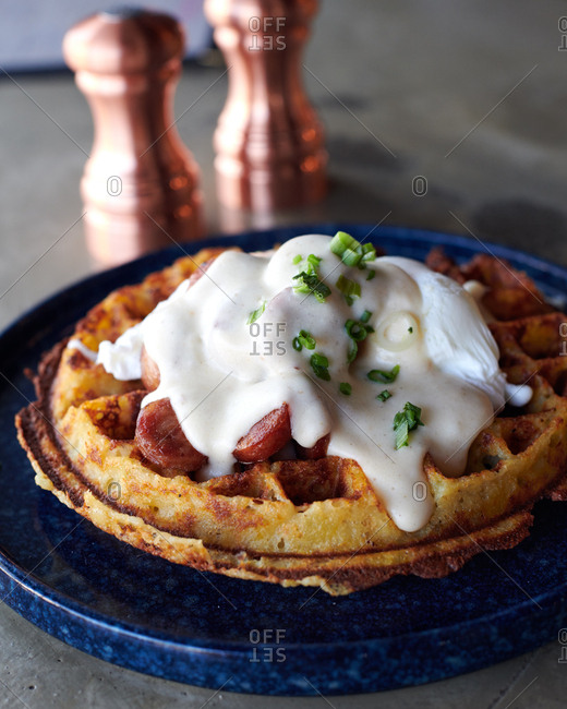 Savory mashed potato waffle with poached egg and covered with gravy and chorizo with cut green onions on a blue plate
