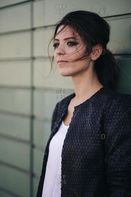 Junge, attraktive, brnette Frau steht vor grnem Garagentor, Halbportrt,