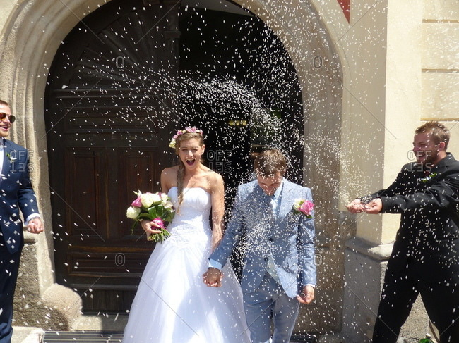 Newlyweds are tossed with rice upon leaving the wedding ceremony