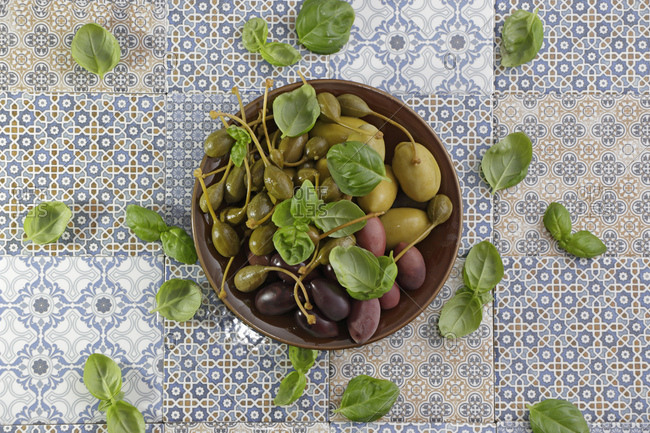 Teller mit Oliven, Kapern und mediterranen Krutern auf blauen gemusterten Fliesen
