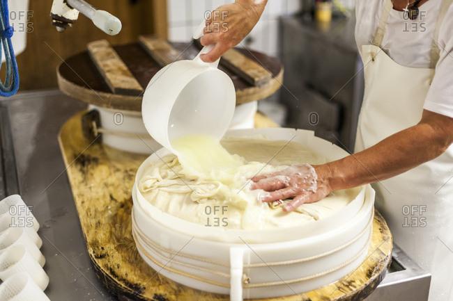 Die Sennerin verarbeitet frische Milch zu wrzigem Alm-Kse, der Ksebruch wird aus dem Kessel gehoben und zu einem Laib weiterverarbeitet,
