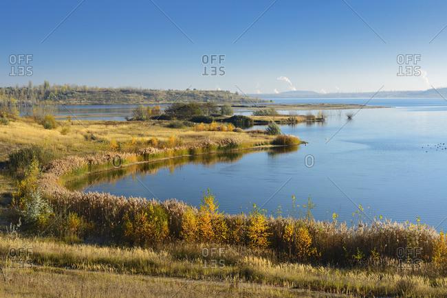 Deutschland, Sachsen-Anhalt, Mcheln, Geiseltalsee im Herbst, grter knstlicher See Deutschlands, hinten die Schornsteine des Chemiestandorts Leuna