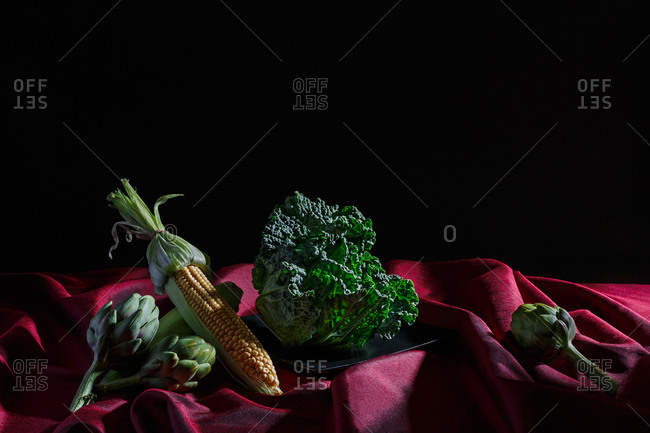 Vegetables on red cloth and black background (cabbage, corn, artichokes).