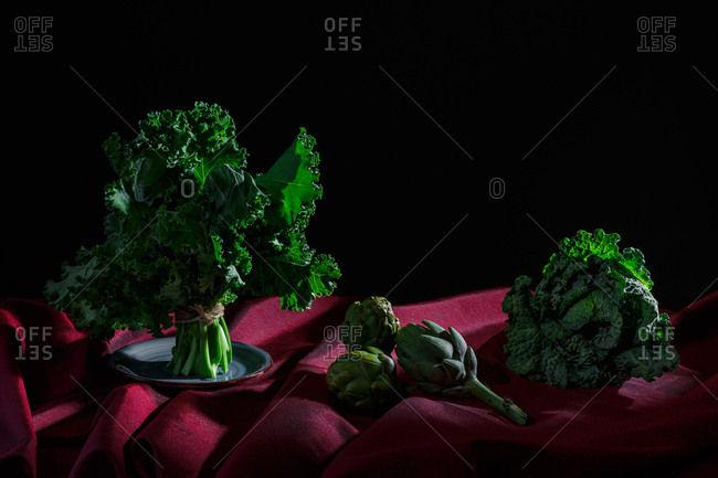 Vegetables on red cloth and black background (cabbage, kale, artichokes).