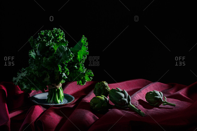 Vegetables on red cloth and black background (kale, artichokes).