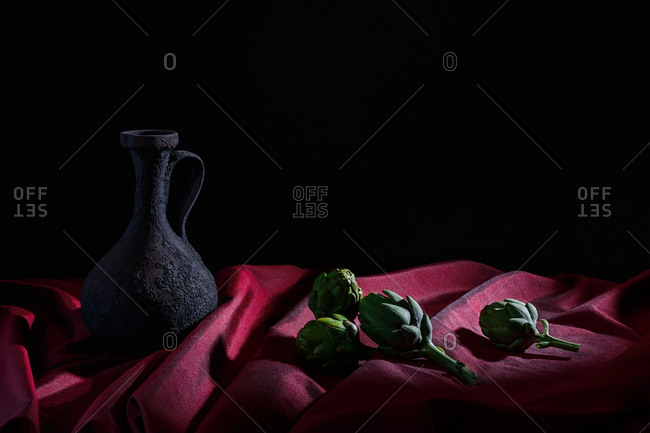 Pitcher and artichokes on red cloth and black background