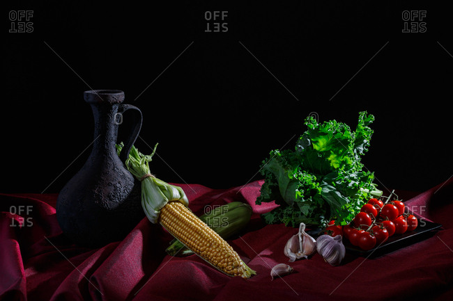 Pitcher and vegetables on red cloth and black background (kale, tomatoes, garlic, corn)