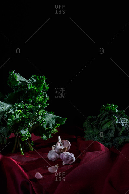 Vegetables on red cloth and black background (kale, cabbage, garlic)