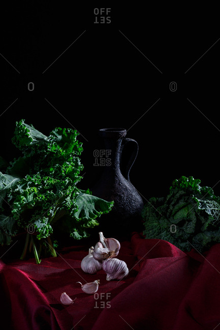 Pitcher and vegetables on red cloth and black background (kale, cabbage, garlic)