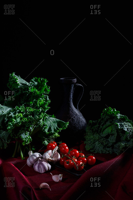 Pitcher and vegetables on red cloth and black background (kale, cabbage, garlic, tomatoes)
