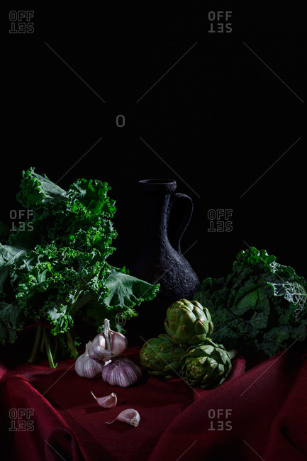 Pitcher and vegetables on red cloth and black background (kale, cabbage, garlic, artichokes)