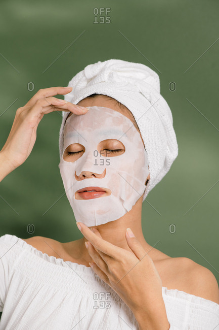 Woman puts on a sheet mask