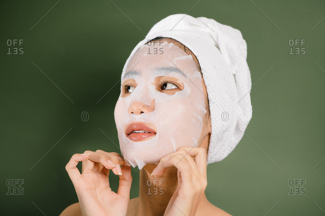 Closeup of Asian woman removing her sheet mask