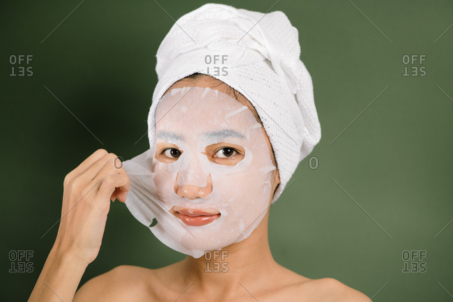 Woman peels off her face mask
