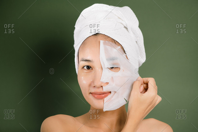 Young beautiful woman removes her face mask