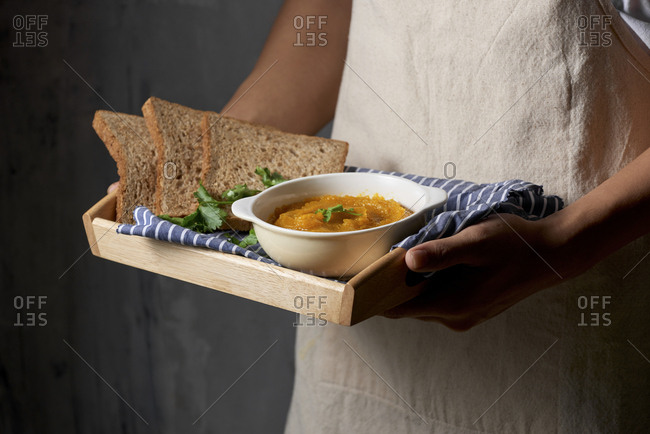 Tray of homemade pumpkin soup served with whole wheat toast