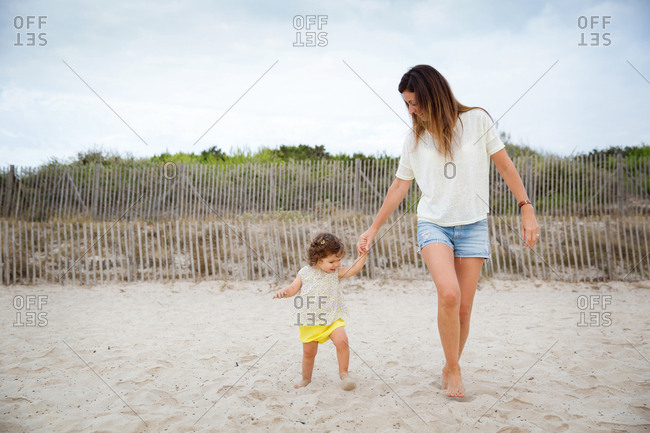Toddler girl holding mother's hand while walking on sand at beach