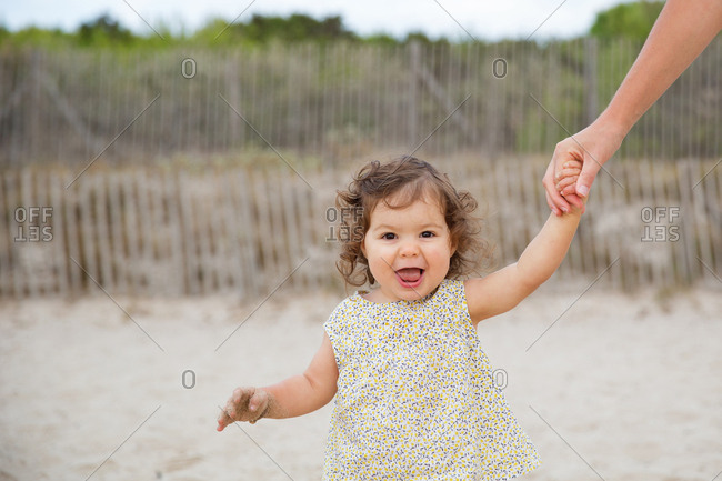 Portrait of happy toddler holding mother's hands while walking on sand at beach