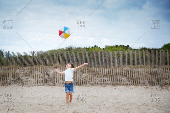 Young boy throwing colorful ball in the air at beach