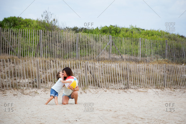 Mother kissing laughing child at beach