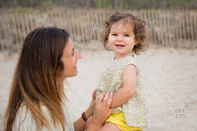 Smiling toddler girl sitting on mother's knees at beach