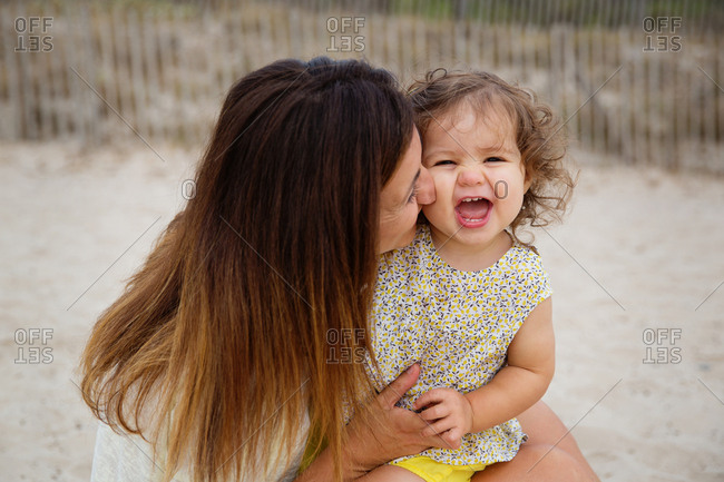 Mother kissing laughing toddler girl at beach
