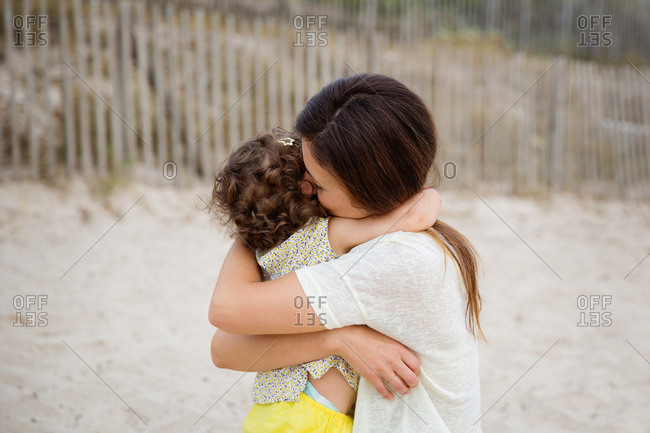 Mother and toddler girl hugging each other at beach