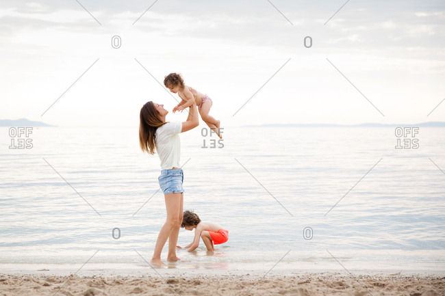 Mother lifting toddler girl at beach while boy playing in sea