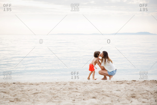 Mother and son kissing each other at beach
