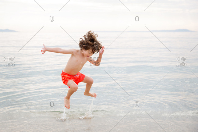 Playful young boy jumping in water at beach