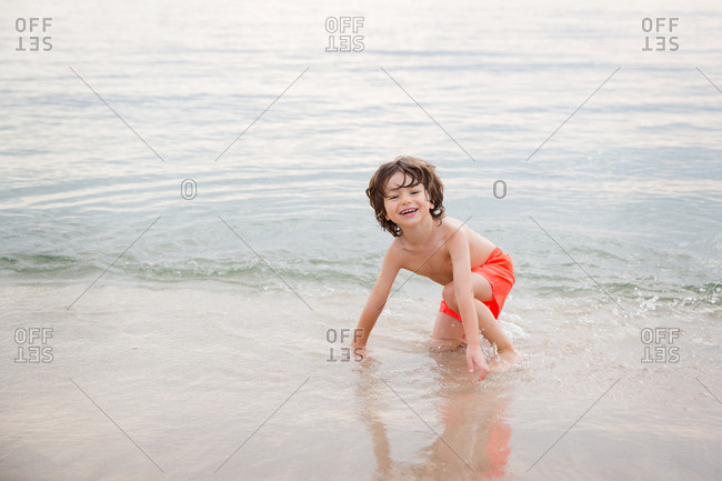 Smiling young boy playing in water at beach