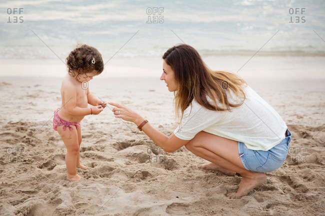 Mother pointing at toddler girl playing with sand at beach
