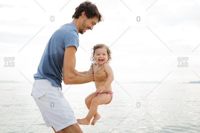 Father holding laughing baby girl at beach