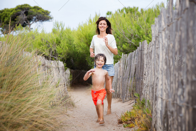 Mother and son playfully running on sandy path at beach