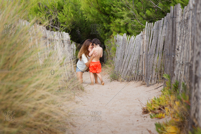 Mother and son laughing together on sandy path at beach