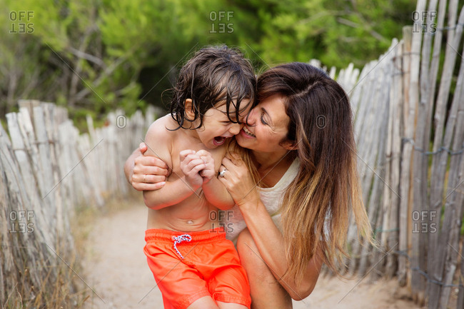 Mother and son cuddling and laughing together on sandy path at beach