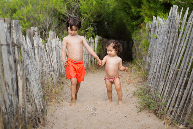 Young boy holding hands with toddler girl at beach